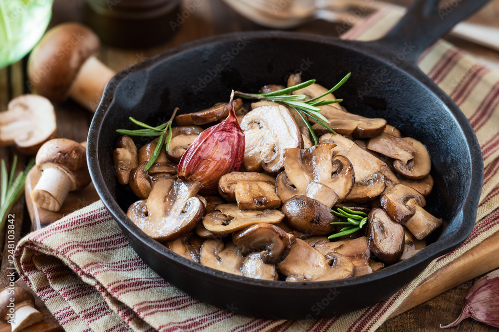 Fototapety, obrazy: Cooked chestnut mushrooms or brown mushrooms in a cast iron skillet with rosemary and a clove of purple garlic