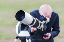 Young Man Looking Skyward Through Astronomical Telescope