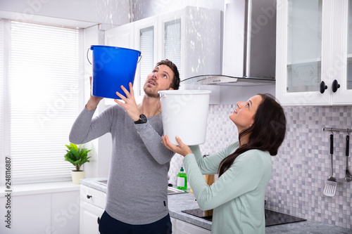 Photo  Couple Collecting Water Leaking From Ceiling In Bucket