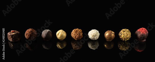 Cuadros en Lienzo Set of fine chocolate candies White, dark and milk chocolate on black background