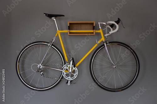 Recess Fitting Bicycle Ein geles Fahrrad an einer Halterung an einer grauen Wand in der Wohnung.