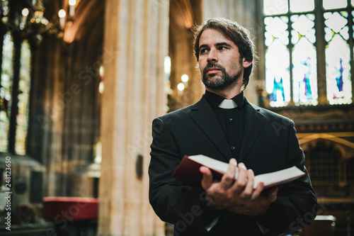Fotografia Christian priest standing by the altar