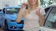 Happy female driver showing thumbs up, holding car keys. Cropped shot of a cheerful woman shopping for new automobile at the dealership. Female client renting auto. Cars concept