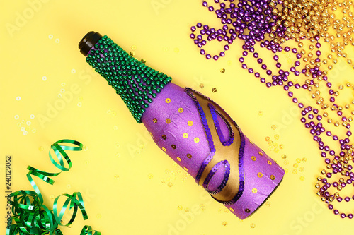 Diy Mardi Gras bottle purple adhesive paper, green bead, carnival mask, sequins yellow background Fototapet