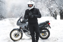 Rider Man And Adventure Motorcycle. Winter Fun. Snowy Day. The Snow Under The Wheels Of A Motorbike. Enduro. Off Road Dual Sport Travel Tour, Active Life Style Concept. Winter Clothes, Equipment