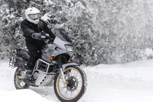 Rider Man In Action On Adventure Motorcycle. Winter Fun. Snowy Day. Ride On Snow Road. Off Road. Dual Sport Travel Tour, Active Life Style Concept. Winter Clothes, Equipment, Copy Spase