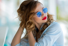 Beautiful Brunette On A Summer Terrace By The Sea, In A Summer Cafe. Talking On A Cell Phone. With Makeup And Hairdo, A Beautiful Smile And Red Lips. The Sun Goggles, Swimsuit