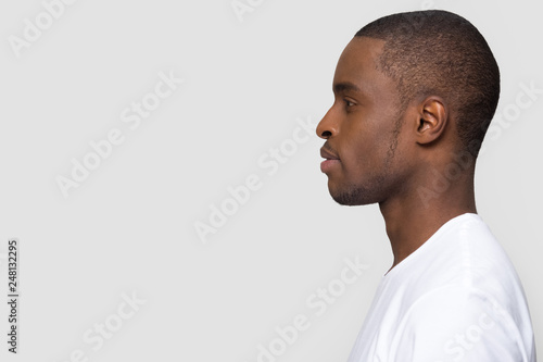 Valokuva  Millennial african man standing in profile isolated on white background
