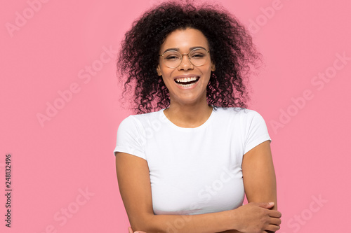 Fototapeta Portrait of joyful black woman laughing isolated on pink background