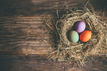 Easter Eggs In Hay Nest On A Rustic Wooden Background