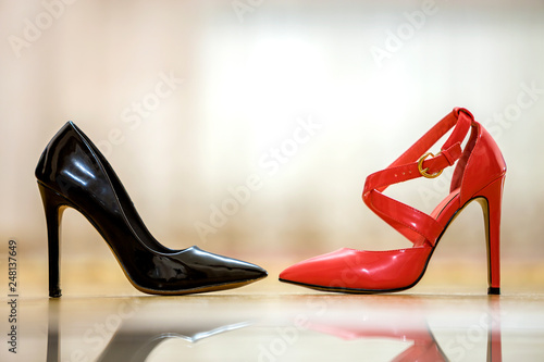 Fotografie, Obraz  Two fashionable comfortable high heel leather female shoes, red and black, isolated on light copy space background