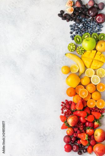 Rainbow fruits berries background on white. Top view of strawberries blueberries cherries mango apple lemons oranges red currants plums blackberries, selective focus Wall mural