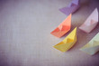 pastel color paper boat on canvas texture background with copy space, learning and education concept