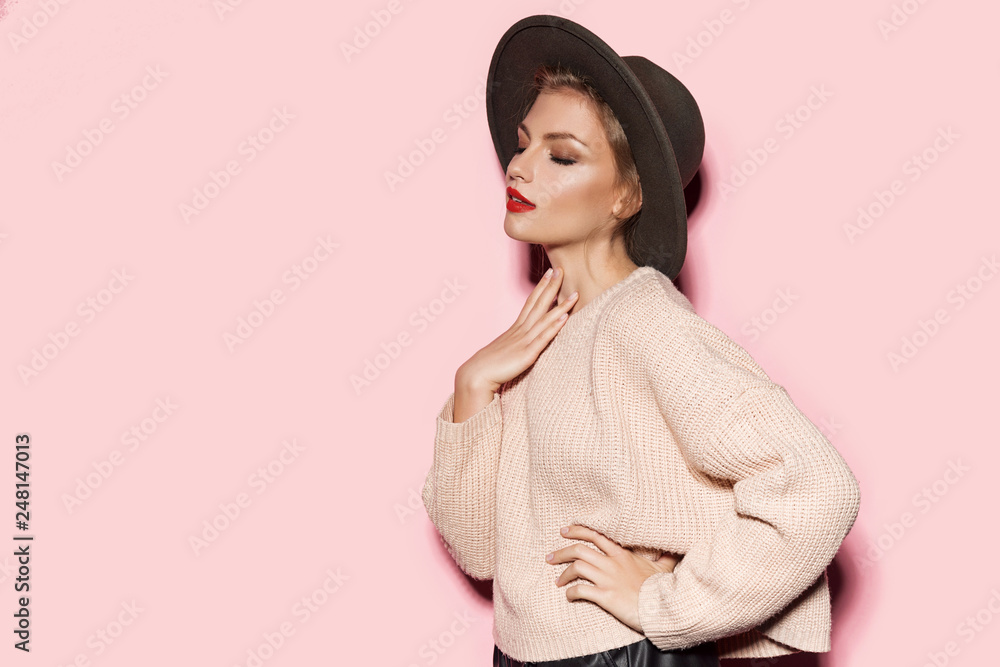 Fototapeta Portrait of attractive well-dressed model in comfy beige sweater and stylish black hat. Modern vogue fashion and autumn concept. Copy space in left side