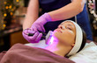 canvas print picture people, beauty, cosmetic treatment, cosmetology and technology concept - beautician with microdermabrasion device doing face exfoliation to young woman lying at spa
