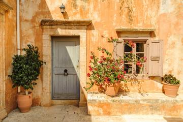 Fototapeta na wymiar Yellow wall of the monastery with doors, window and flowerpots