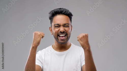 Fotografía  success, emotion and expression concept - happy young indian man celebrating vic