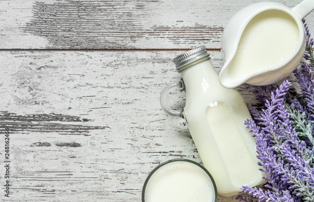 Fototapety, obrazy: Vintage glass bottle with milk, a glass with milk and a beautiful white jug next to a branch of lavender flowers on a vintage wooden background. View from above.