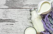 Vintage Glass Bottle With Milk, A Glass With Milk And A Beautiful White Jug Next To A Branch Of Lavender Flowers On A Vintage Wooden Background. View From Above.