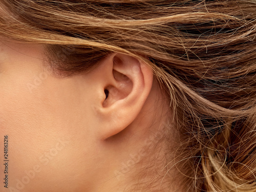 Fotografija health, people and beauty concept - close up of young woman face from ear side