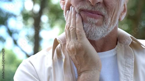 Fotografie, Obraz  Senior man having problem with teeth, social program of dental prosthetics
