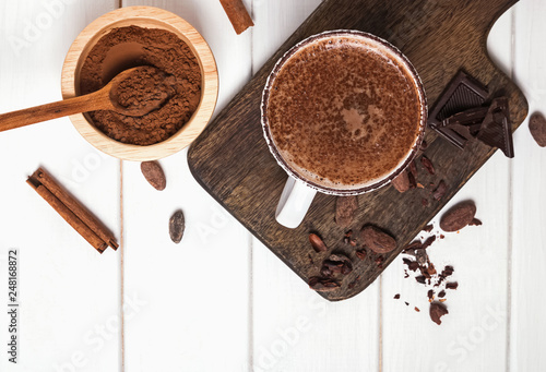 Foto op Plexiglas Chocolade Hot chocolate in the cup, cocoa beans and powder on the white wooden table