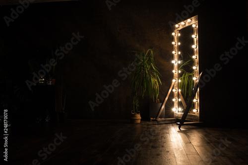 Obraz na plátně  Toilet mirror stands on a wooden floor with light bulbs for lighting
