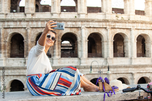 Photo  Beautiful young woman taking selfie pictures with smartphone sitting in front of colosseum in Rome at sunset