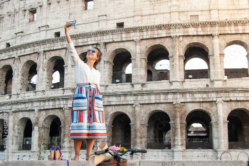 Photo  Beautiful young woman taking selfie pictures with smartphone standing in front of colosseum in Rome at sunset