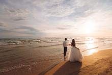 Elegant Gorgeous Bride And Groom Walking On Ocean Beach During Sunset Time. Romantic Walk Newlyweds On Tropical Island