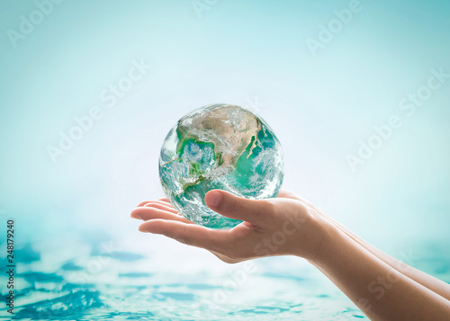 World ocean day, saving water campaign, sustainable ecological ecosystems concept with green earth on woman's hands on blue sea background : Element of this image furnished by NASA Fototapete
