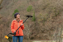 Attractive Girl With A Smile And A Dreamy Gaze,posing With A Metal Detector And Mountain In The Background