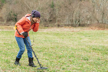 Young Woman Enthusiastically Explores The Soil With A Detector