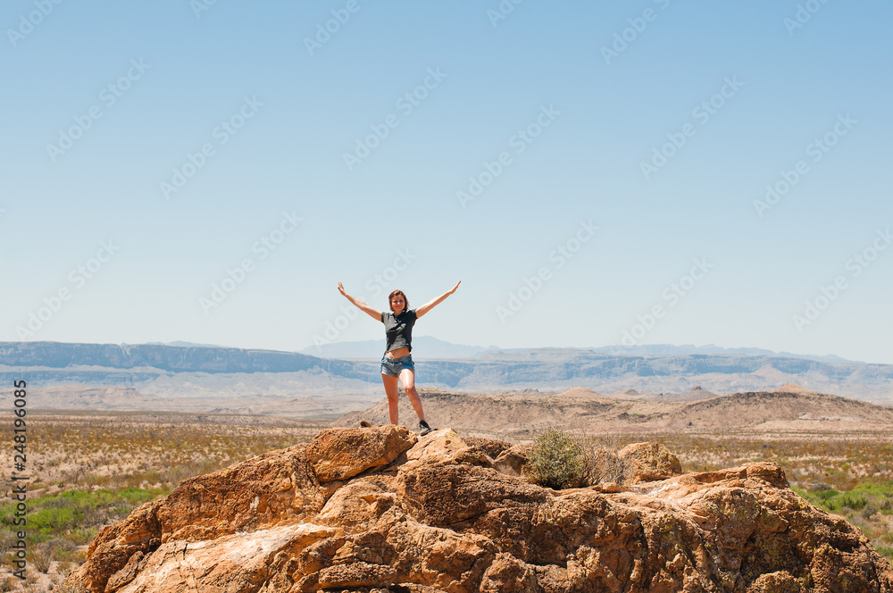 Fototapety, obrazy: A woman standing on a rock with lifted hands up over the mountains of a Texas desert