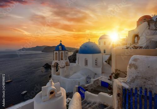 Foto auf Leinwand Santorini Romantischer Sonnenuntergang über dem malerischem Dorf Oia auf der Insel Santorini, Kykladen, Griechenland