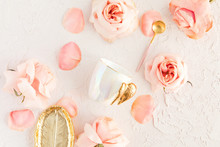 Stylish Coffee Or Tea Set On Pastel Background With Pink Flowers, Leaf Golden Plate And Spoon With Roses And Petals. Flatlay, Top View On Pastel Concrete Background