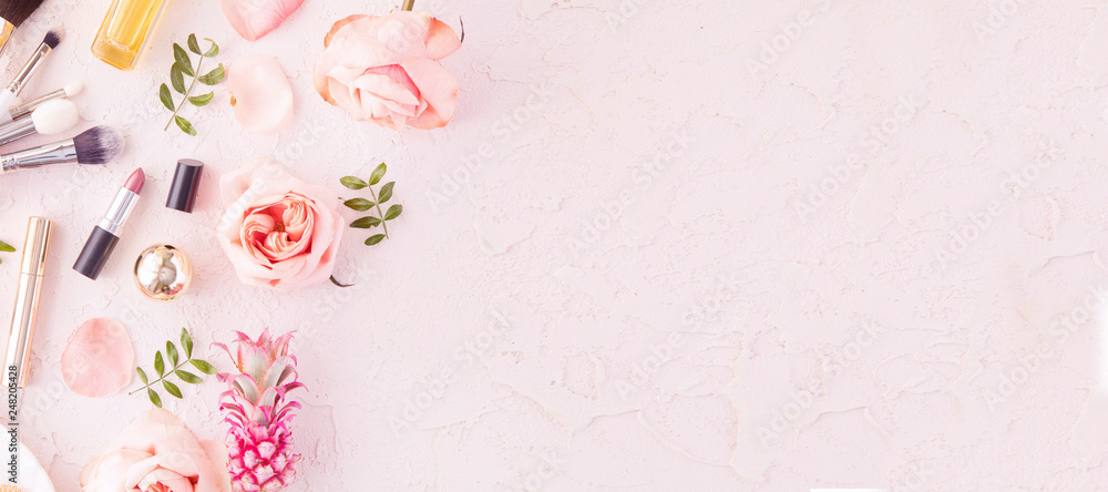 Fototapeta Makeup products and make-up brush with pink flowers on pastel background. Panoramic banner with copy space for text. Luxury beauty.