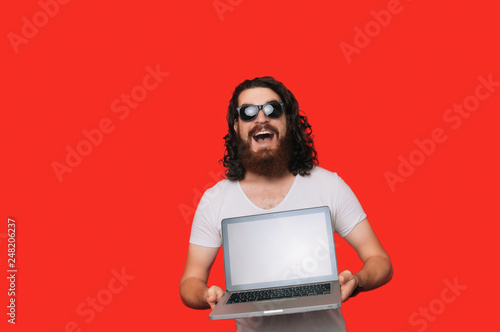 Happy cool bearded man in white shirt showing laptop