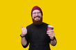 Young cheerful and stylish handsome bearded man is enjoying his day off with coffee