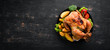 Baked chicken with potatoes and vegetables on a black background. The traditional dish for Thanksgiving. Top view. Free copy space.