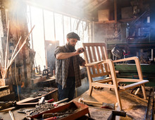 A Craftsman In His Workshop Working On An Armchair Frame