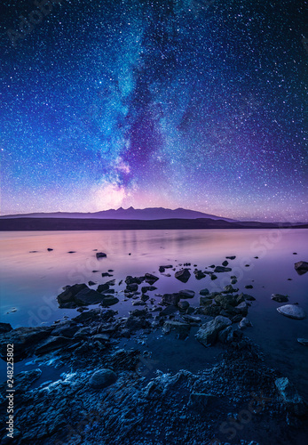 Obraz Colorful milky way galaxy over the lake and mountain. Beautiful night landscape. - fototapety do salonu