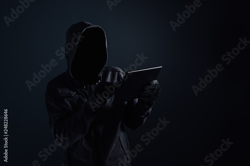 Fotografía  Hooded computer hacker with obscured face using digital tablet