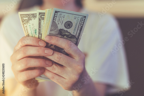 Photo Casual woman is counting american dollar banknotes