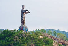 Silhouetted Against The Evening Sky, The Cristo Rei Is A 27 Meter High Statue Of Jesus Located Atop A Globe In Dili, East Timor.