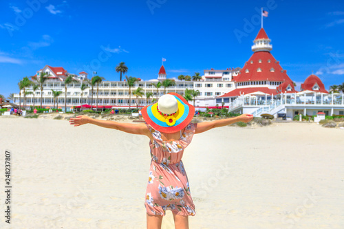 Fototapeta  Carefree woman in hat on Coronado Central Beach, looking historic Victorian hotel on Coronado Island, San Diego