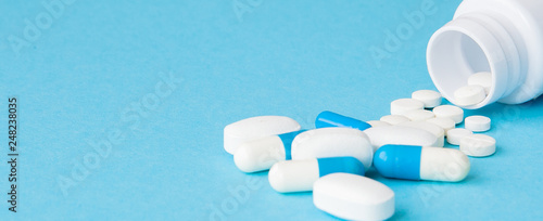 Photo sur Toile Pharmacie Close up pills spilling out of pill bottle on blue background. Medicine, medical insurance or pharmacy concept