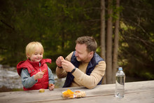 Little Boy And His Father Eating Snacks During Picnic On Coast Of Mountain River In Switzerland.