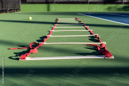 Photo Agility ladder lying on tennis court waiting for next player to improve the footwork skills