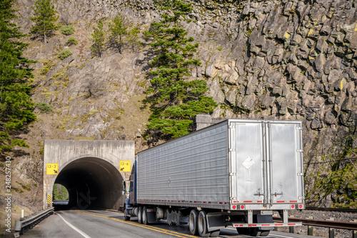 Zdjęcie XXL Duża ciężarówka pół ciężarówki z naczepą chłodni porusza się po drodze z tunelem przez skałę